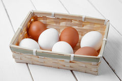 Raw brown chicken eggs on a wooden white background. Royalty Free Stock Photography