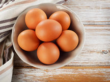 Raw brown eggs in a bowl. Stock Photos