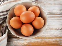 Raw brown eggs in a bowl. Selective focus Stock Photos
