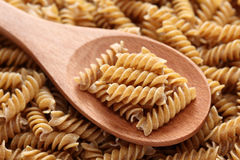 Raw brown pasta on a wooden spoon. Raw brown pasta (Fusilli) on a wooden spoon on a fusilli background. Close-up Royalty Free Stock Photo
