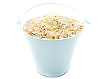 Raw brown rice in white bucket. On white isolated background Stock Photos