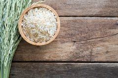 Raw brown whole grain semi-milled rice in wood bowl with paddy on wooden table. Top view with copy space royalty free stock photography
