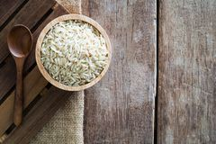 Raw brown whole grain semi-milled rice in wood bowl with wood spoon on gunny sack cloth on wooden table. Top view with copy space royalty free stock image