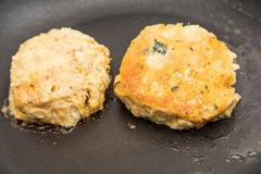 Raw and Browned Crab Cakes in Pan Stock Image