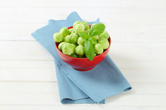 Raw Brussels sprouts. Bowl of raw Brussels sprouts on blue place mat Stock Photography