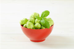 Raw Brussels sprouts. Bowl of raw Brussels sprouts on white background Royalty Free Stock Image