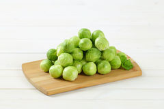 Raw Brussels sprouts. Heap of raw Brussels sprouts on wooden cutting board Royalty Free Stock Image