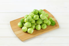 Raw Brussels sprouts. Heap of raw Brussels sprouts on wooden cutting board Stock Images