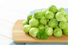 Raw Brussels sprouts. Heap of raw Brussels sprouts on wooden cutting board - close up Royalty Free Stock Photos