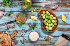 Raw brussels sprouts with ingredients for cooking healthy food. Raw brussels sprouts with ingredients for cooking tasty and healthy food on wooden table, top Royalty Free Stock Photos