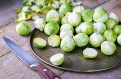 Raw brussels sprouts on old metal plate on rustic table. Raw brussels sprouts on old metal plate and rustic table Royalty Free Stock Photo