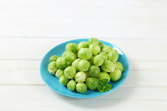 Raw Brussels sprouts. Plate of raw Brussels sprouts on white background Royalty Free Stock Images