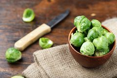 Brussels sprouts on a wooden background. Raw brussels sprouts in a plate on a wooden background, space for text Royalty Free Stock Image