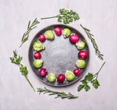 Raw Brussels sprouts and radishes with herbs in a frying pan on wooden rustic background top view close up place text,frame. Raw Brussels sprouts and radishes Royalty Free Stock Photo
