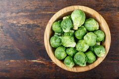 Raw Brussels sprouts. In a plate on a wooden background, space for text Royalty Free Stock Photo