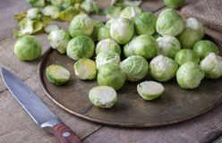 Raw brussels sprouts on rusty steel plate with knife on wooden rustic desk during sunny day. Stock Photos