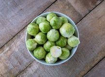 Raw brussels sprouts in white bowl on wooden desk. Top view. Raw brussels sprouts in white bowl on wooden desk Royalty Free Stock Image