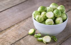 Raw brussels sprouts in white bowl on wooden rustic desk. Stock Image
