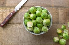 Raw brussels sprouts in white bowl on wooden rustic desk. Raw brussels sprouts in white bowl on wooden rustic desk with knife on left side Stock Images
