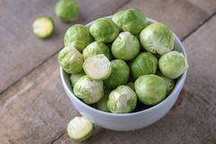Raw brussels sprouts in white bowl on wooden rustic desk. R Stock Photos