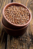 Raw buckwheat. In bowl on wooden background stock photo
