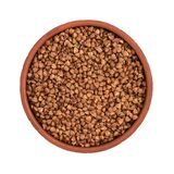 Raw buckwheat in a brown bowl isolated on white background, top view