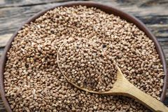 Raw buckwheat groats in a wood plate on a buckwheat background. next to the plate is a wooden spoon. Space for text stock image