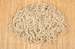 Raw Buckwheat Noodles #6. Bunch of soba noodles on a bamboo mat Royalty Free Stock Photo