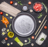 Raw buckwheat noodles with vegetables, ginger, chopsticks and ingredients, laid out around the pan place for text,frame on wooden Stock Photo