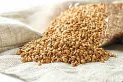 Raw buckwheat is strewed from the package on sacking on a wooden background. Healthy diet food. Stock Image