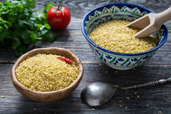 Raw bulgur grains in a bowl. Raw bulgur wheat grains in colorful arabic bowl, fresh parsley, tomato and peppers for cooking. Wooden table background, horizontal Royalty Free Stock Photo
