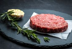 Raw burger beef patty on stone background Royalty Free Stock Photo