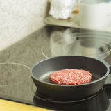 Raw burger being cooked on a pan Royalty Free Stock Photo