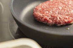 Raw burger being cooked on a pan Royalty Free Stock Photography