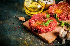 Raw burger cutlets. With salt, pepper, oil, herbs and spice, on dark table, copy space Stock Photos