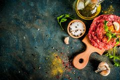 Raw burger cutlets. With salt, pepper, oil, herbs and spice, on dark table, copy space top view Royalty Free Stock Photos