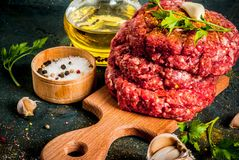 Raw burger cutlets. With salt, pepper, oil, herbs and spice, on dark table, copy space Royalty Free Stock Images