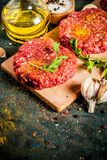 Raw burger cutlets. With salt, pepper, oil, herbs and spice, on dark table, copy space Stock Photography
