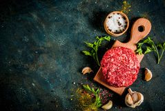 Raw burger cutlets. With salt, pepper, oil, herbs and spice, on dark table, copy space top view Stock Image