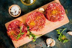 Raw burger cutlets. With salt, pepper, oil, herbs and spice, on dark table, copy space top view Stock Photo