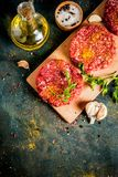Raw burger cutlets. With salt, pepper, oil, herbs and spice, on dark table, copy space top view Royalty Free Stock Photo