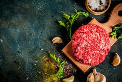 Raw burger cutlets. With salt, pepper, oil, herbs and spice, on dark table, copy space top view Stock Images