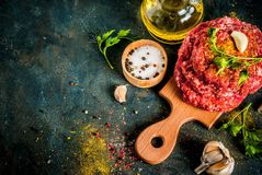 Raw burger cutlets. With salt, pepper, oil, herbs and spice, on dark table, copy space top view Royalty Free Stock Image