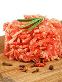 Raw Burger. Fresh Raw Beef Burger with Rosemary and Pepper Corns on Wooden Cutting Board  on white background Stock Photo