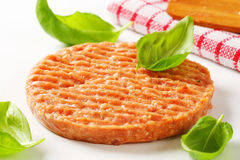 Raw burger patty. With fresh basil leaves Royalty Free Stock Photography