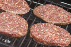 Raw  Burgers on a Barbecue Stock Photo