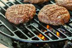 Raw burgers on barbecue grill with fire Royalty Free Stock Photography