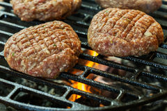 Raw burgers on barbecue grill with fire Stock Image