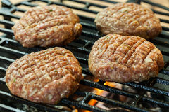 Raw burgers on barbecue grill with fire Royalty Free Stock Image