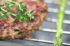 Raw burgers on bbq barbecue grill with fire. Food meat - raw burgers on bbq barbecue grill with asparagus . Shallow dof stock images